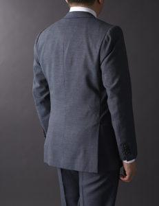 ジャストフィットしたスーツの上着。肩甲骨から腰にかけての曲線がきれいだ。